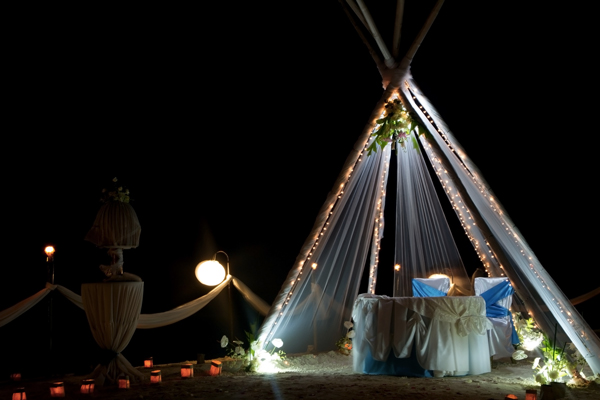 wedding arch and set up with flowers on tropical beach at night